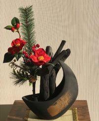 漆黒の炭に迎春花が鮮やかです